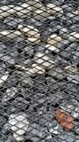 Stones in the steel cage, decorated the wall. Royalty Free Stock Images