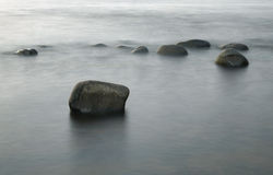 Stones in Surf Long Exposure Photo Royalty Free Stock Images