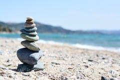 Stones pyramid on sand, beach landscape symbolizing zen and balance in life stock photography