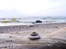 Stones tower on wood on sea coast. Oval stones tower on Baltic sea coast, Lithuania stock photography