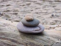 Stones tower on wood on sea coast. Oval stones tower on sea coast, Lithuania royalty free stock photos