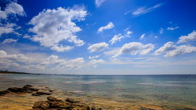 Stones in Transparent Shallow Azure Sea Blue Sky White Clouds stock video footage