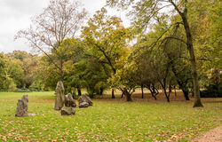 Stones and trees in the park in autumn. Stones and yellow and green trees in the park in autumn Royalty Free Stock Photos