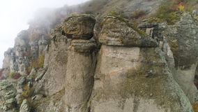 Stones of unusual forms on the mountain covered with fog clouds. Shot. Aerial view for foggy day in the mountains and