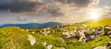 Stones in valley on top of mountain range at sunset Royalty Free Stock Images