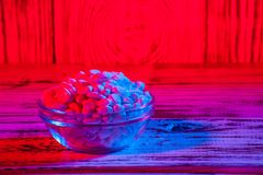 Stones in a vase on wooden blue red purple gradient background. Close up Royalty Free Stock Photos