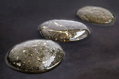 Stones in water. Stepping Stones on black water background Stock Photos