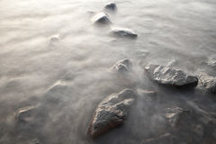 Stones in water. Photographed at long exposure Stock Images