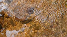 The stones in the water are clearly visible and the water is clear royalty free stock image