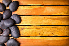 Stones with water drops on the left side on wooden Royalty Free Stock Photo