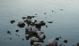 Stones in the water. On the evening beach stock image