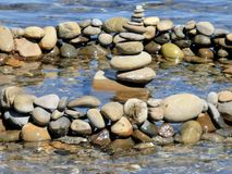 Stones in the water Pyramide von Kiesel. Stones water sky blue sea seascape siliceous Pyramide von Kiesel stock images