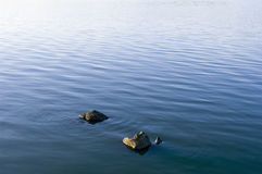 Stones in water surface. Stones emerging from a beautiful smooth water surface Royalty Free Stock Images