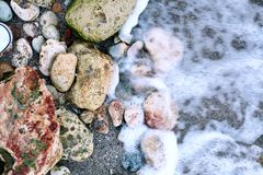 Stones and a wave. Color shot of some stones being washed by a wave Royalty Free Stock Photography