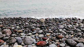 Stones with waves on beach of shore or coast of ocean or sea stock footage