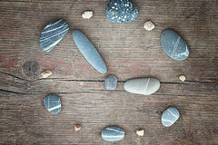 Stones on a wooden background, the concept of equilibrium The burden hours. Clock Stock Photo