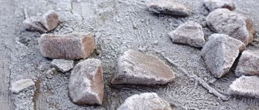 Stones on a wooden base covered with hoarfrost. Winter frosty background.  stock photo