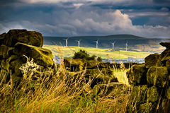 Stonewall with distance wind turbines and clouds Stock Photos