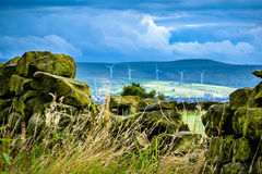 Stonewall with distance wind turbines and clouds Royalty Free Stock Image