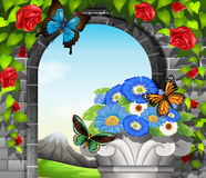 A stonewall with flowering plants and butterflies. In garden Stock Photography