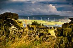 Stonewall met de turbines van de afstandswind en wolken Stock Foto's