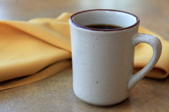 Stoneware coffee cup and cloth napkin on table Royalty Free Stock Image