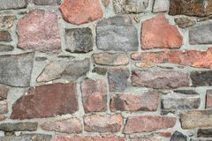 Stonework wall in rows with mortar in many colors. Stonework in rows with mortar in reds and grays Stock Image