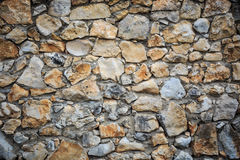 Stonework wall background with green and brown rough stones of d Royalty Free Stock Photos