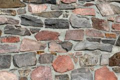 Stonework wall in rows with mortar in many colors. Stonework wall in rows with mortar in reds, browns and grays Royalty Free Stock Image