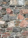 Stonework wall in rows with mortar in many colors. Stonework in rows with mortar in reds and grays Stock Images