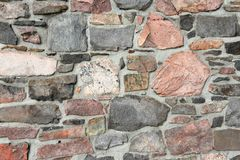 Stonework wall in rows with mortar in many colors. Stonework wall in rows with mortar in reds, browns and grays Royalty Free Stock Photo
