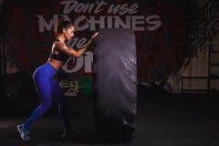 Stong与拖拉机轮胎的女孩锻炼在健身房 图库摄影