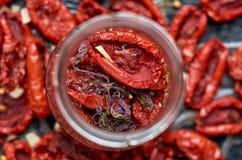 Stoni con molti pomodori e spezie rossi secchi su una fine scura della superficie su Fondo vago struttura secco dei pomodori Fotografie Stock Libere da Diritti