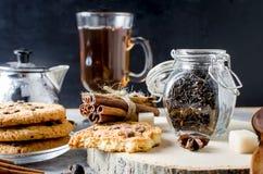 Stoni con tè, i biscotti casalinghi e le spezie per tè sul BAC scuro Immagini Stock