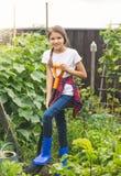 Stonowana fotografia piękna nastoletniej dziewczyny głębienia ziemia w ogródzie z rydlem fotografia stock