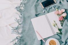 Stonowanego mieszkania nieatutowa pastylka, telefon, filiżanka kawy i kwiaty na białej koc z turkusową szkocką kratą, zdjęcie stock