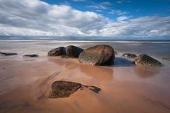 Stony Baltic Sea beach. And old lighthouse stock images