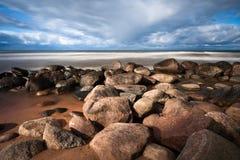 Stony Baltic Sea beach. And old lighthouse royalty free stock photos