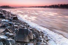 Stony bank of a freezing river covered in fog during dusk Royalty Free Stock Photo