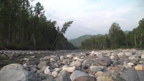 Stony bank of a mountain river. Panoramic survey along the coast stock footage