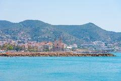 Stony beach and church of Sant Bartomeu and Santa Tecla in Sitges, Barcelona, Catalunya, Spain. Copy space for text. Royalty Free Stock Photo