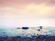 Stony beach in island in romantic colors of tropical sunset Stock Photos