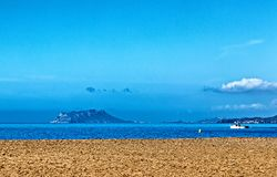 A stony beach looking out to an island. With a fishing boat royalty free stock photography