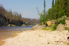 A stony beach in the northwest territories. A peaceful spot at a waterfall near fort simpson in northern canada Stock Photo