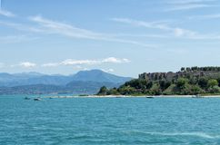Stony Beach of Sirmione town on Garda Lake with view of Grottoes of Catullus. royalty free stock image