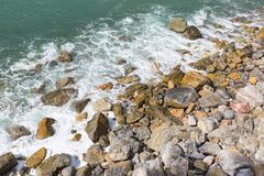 Stony beach, turquoise color water, waves,white foam, Mediterranean Sea, Cinque Terre, Italy.  stock image
