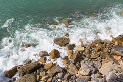 Stony beach, turquoise color water, waves,white foam, Mediterranean Sea, Cinque Terre, Italy.  royalty free stock photography