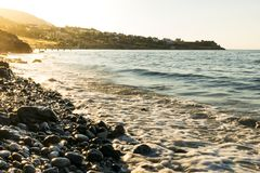 Stony beach with waves. Stony beach with waves and with golden colored sun lights in the evening stock photography