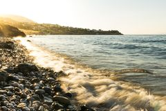 Stony beach with waves. Stony beach with waves and with golden colored sun lights in the evening royalty free stock image