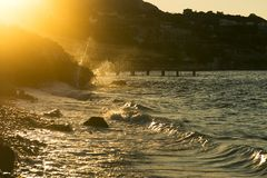Stony beach with waves. Stony beach with waves and with golden colored sun lights in the evening stock photo